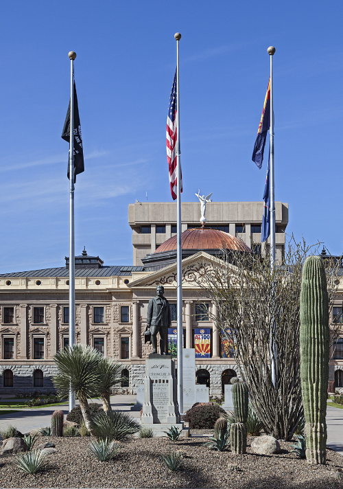 Three flags flying in the foreground in front of the Arizona State Capitol building