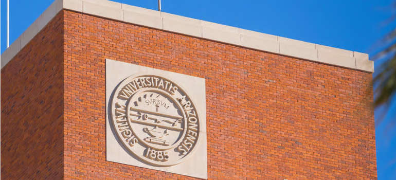 Tight shot of the University of Arizona seal engraved and mounted at the top of the Administration Building which is made of red brick